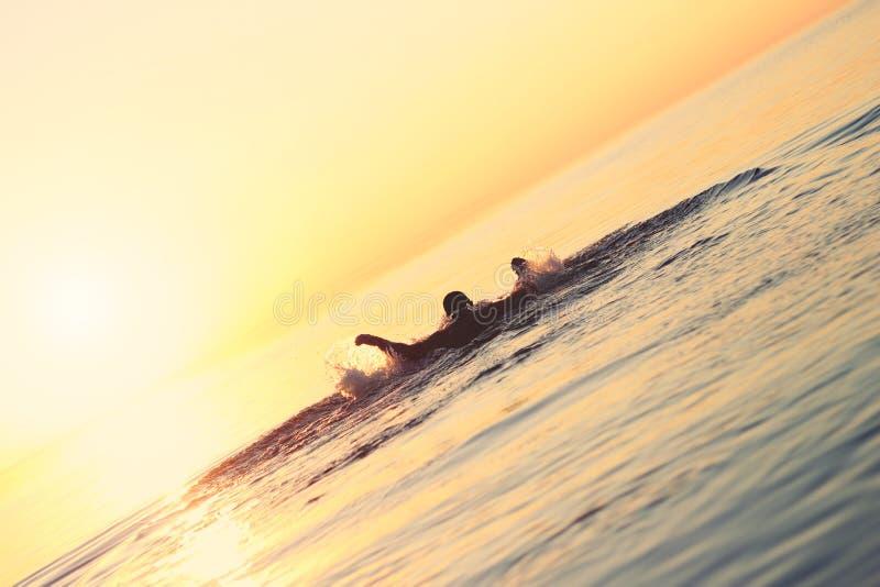 Sterke atleet die in het water bij zonsondergang zwemmen stock afbeelding