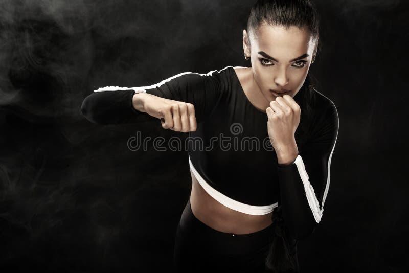 Sterke atletisch, vrouwenbokser, die bij opleiding op de zwarte achtergrond in dozen doen Sport het in dozen doen Concept met exe stock afbeeldingen