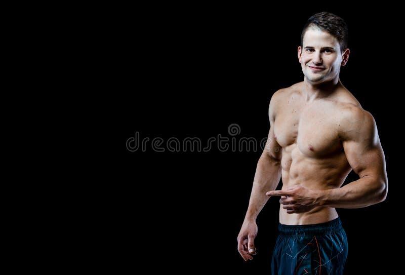 Sterke Atletische Mens die spierlichaam en sixpack abs over zwarte achtergrond tonen royalty-vrije stock foto's