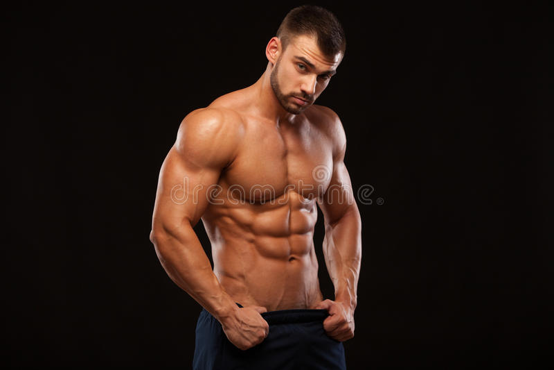 Sterke Atletische Mens - Geschiktheids Model tonend Torso met zes pakkenabs de tribunes rechtstreeks en zet van hem indient broek royalty-vrije stock foto's