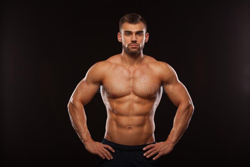 Sterke Atletische Mens - Geschiktheidsmodel die zijn Torso met zes pakkenabs tonen Geïsoleerd op Zwarte Achtergrond met Copyspace stock foto's
