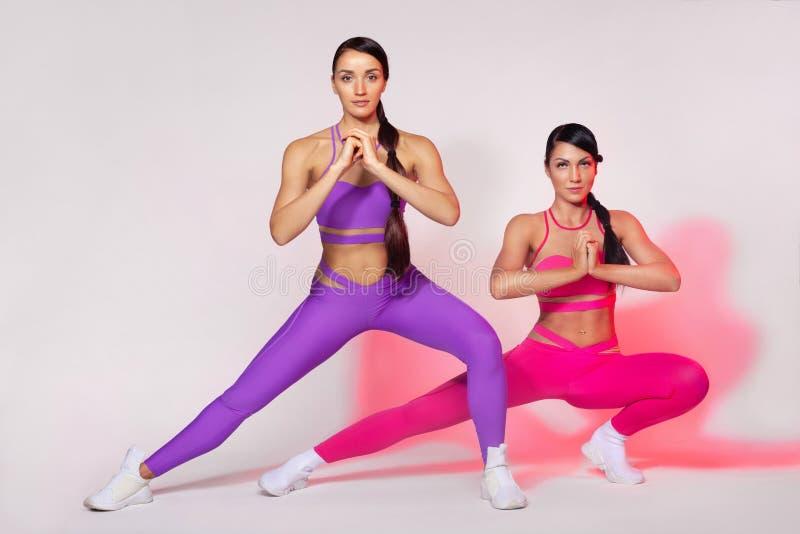 Sterke atletische vrouw, die oefening op witte achtergrond doen die sportkleding dragen Fitness en sportmotivatie stock foto