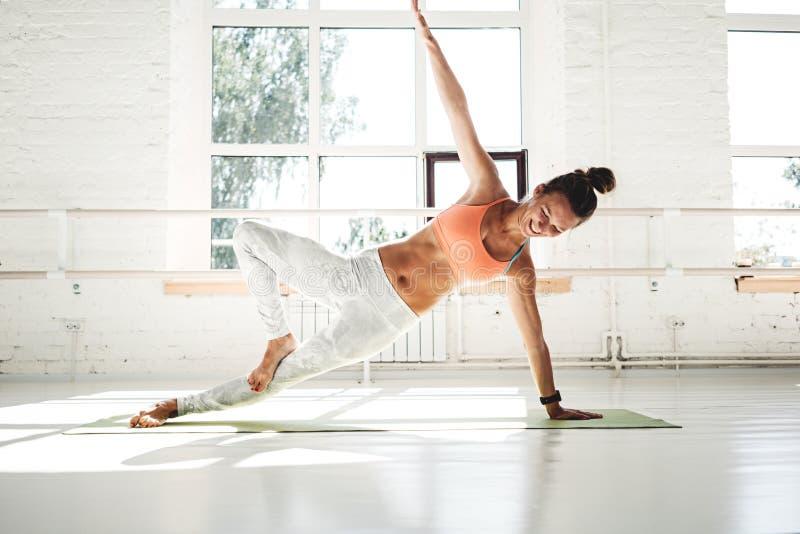 Sterke atletische vrouw die uitrekkende training op yogamat doen in zonnige witte gymnastiek stock foto's