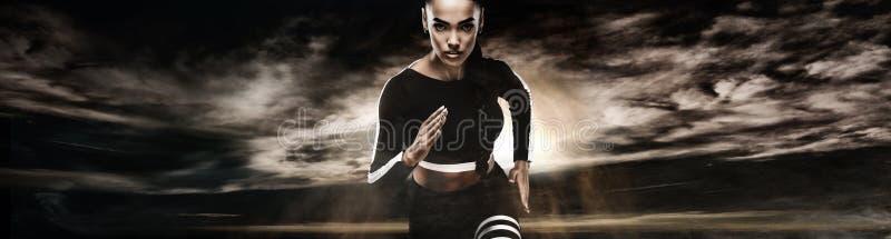 Sterke atletische vrouwensprinter, die op donkere achtergrond lopen die in sportkleding dragen Fitness en sportmotivatie agent royalty-vrije stock fotografie