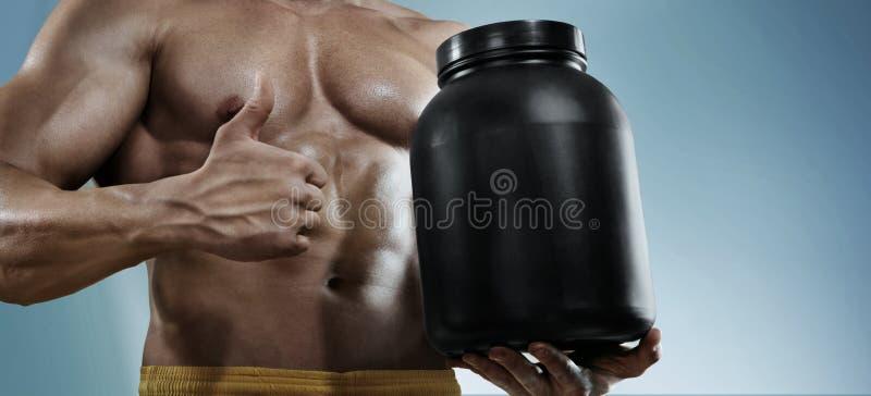 Sterke bodybuilder die een plastic kruik met een droge proteïne houden en gebaar tonen stock afbeelding