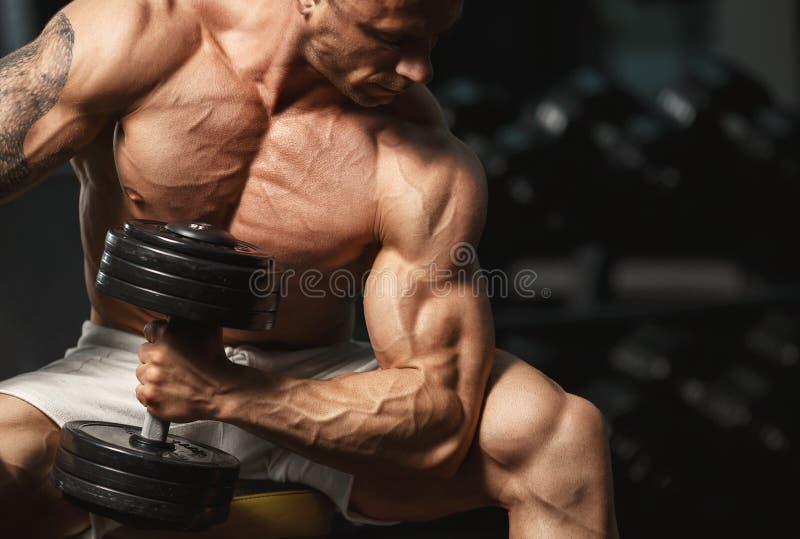 Sterke bodybuilder die oefening met domoor doen stock afbeeldingen