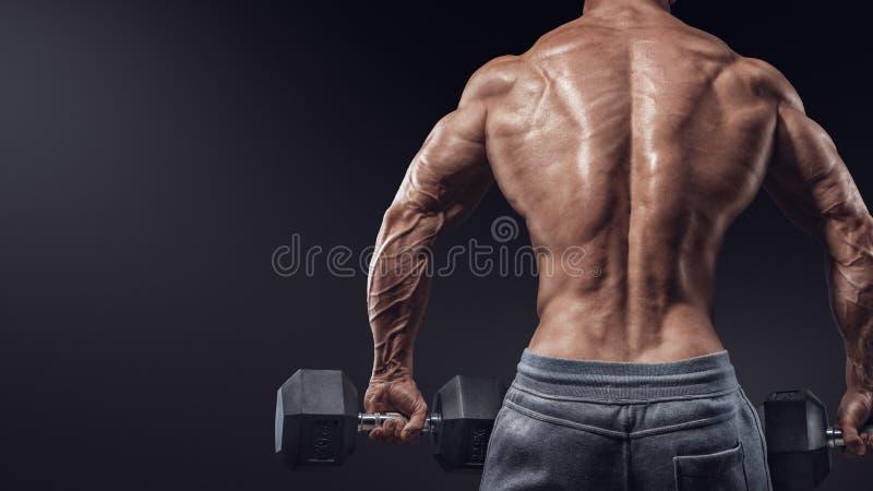 Sterke bodybuilder die oefeningen met omgeslagen domoren doen royalty-vrije stock afbeeldingen
