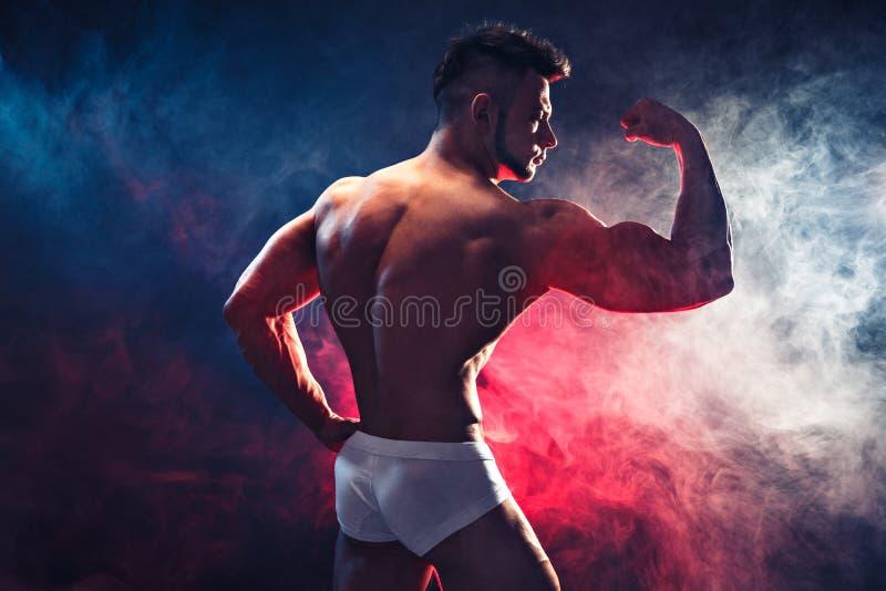 Sterke Bodybuilder Mens met perfecte abs, schouders, bicepsen, triceps en borst, de persoonlijke verbuiging van de geschiktheidst royalty-vrije stock foto