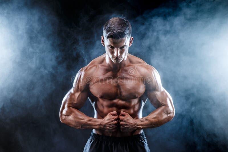 Sterke bodybuildermens met perfecte abs, schouders, bicepsen, triceps, borst stock afbeeldingen