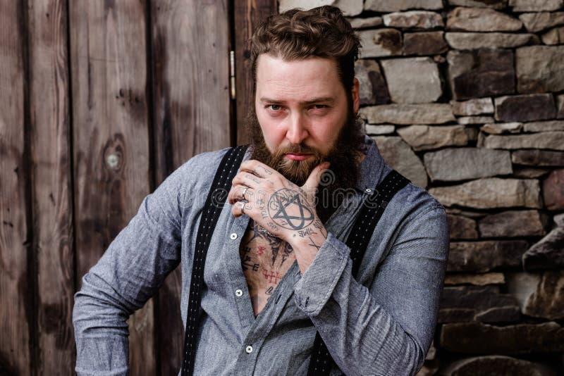 Sterke brutale mens met een baard en tatoegeringen op zijn handen gekleed in modieuze vrijetijdskledingstribunes op de achtergron stock foto's