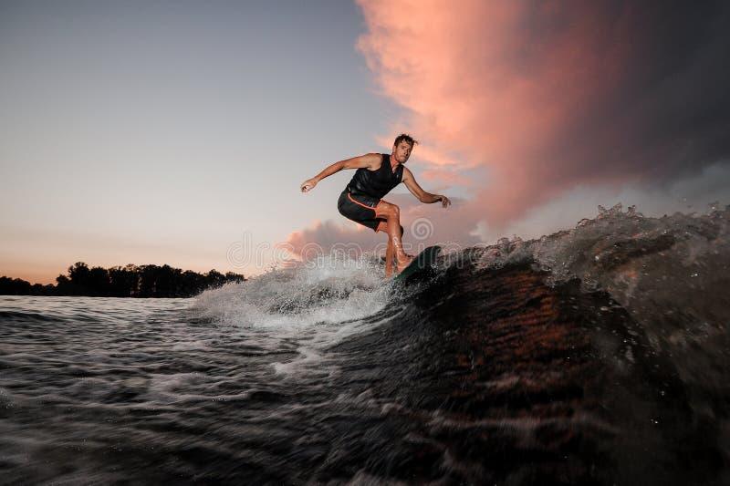 Sterke en jonge wakesurfer die op riviergolven bij de zonsondergang berijden royalty-vrije stock afbeelding
