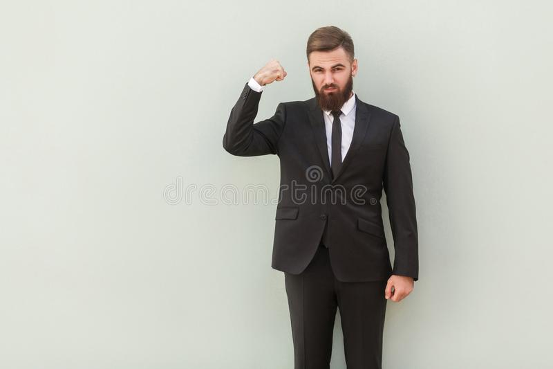 Sterke, ernstig gebaarde zakenman die spier en het kijken tonen stock foto