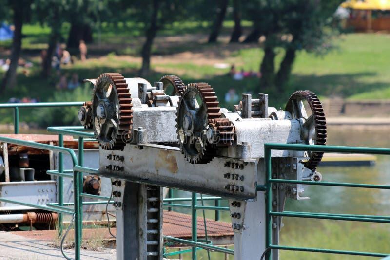 Sterke geroeste die metaaltoestellen worden gebruikt om en metaalplaat op te heffen te verminderen die waterstroom aan dam verhin stock afbeeldingen