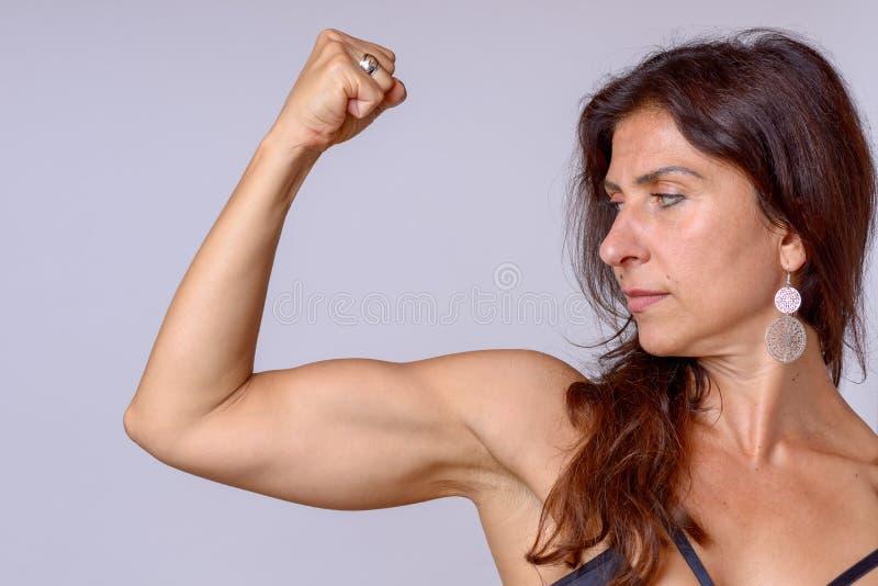Sterke geschikte rijpe vrouw die haar wapenspieren buigen stock foto's