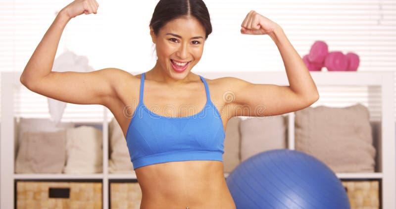 Sterke Japanse vrouw die met spieren pronken stock fotografie