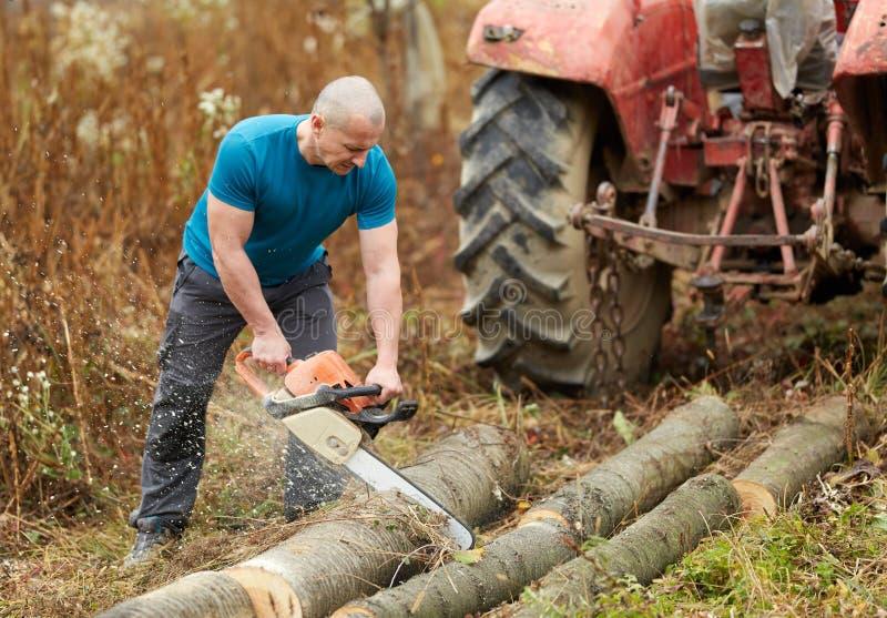 Sterke landbouwer met kettingzaag stock afbeeldingen