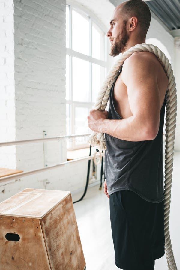 Sterke mannelijke atletenholding op schouderkabel na intense training verticaal royalty-vrije stock foto