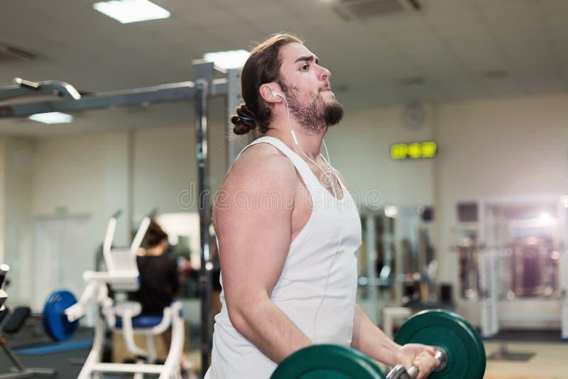 Sterke mens, bodybuilder die met barbell in een gymnastiek uitoefenen royalty-vrije stock afbeelding