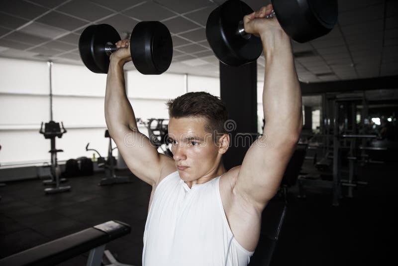 Sterke mens, bodybuilder die met domoren in een gymnastiek uitoefenen stock foto's
