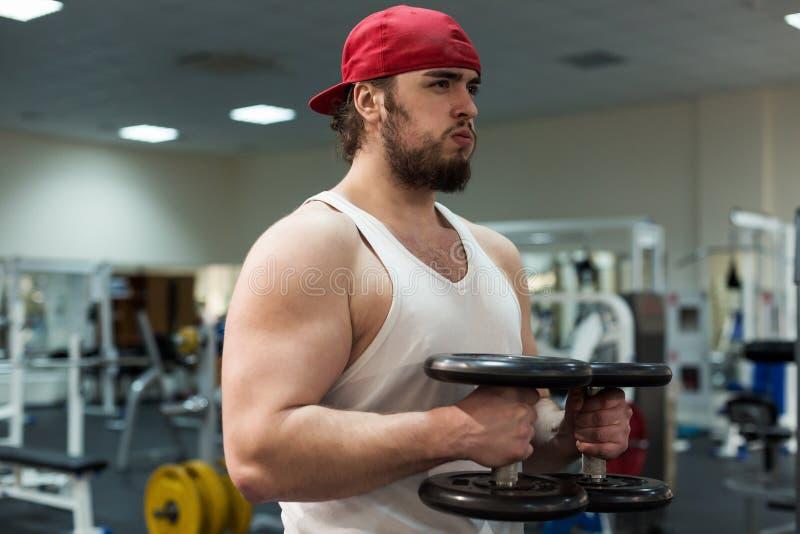 Sterke mens, bodybuilder die met domoren in een gymnastiek uitoefenen stock fotografie