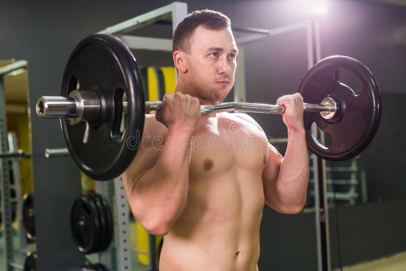 Sterke mens - bodybuilder met domoren in een gymnastiek, die met een barbell uitoefenen stock afbeelding