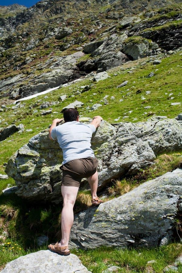 Sterke mens die berg beklimt stock afbeelding