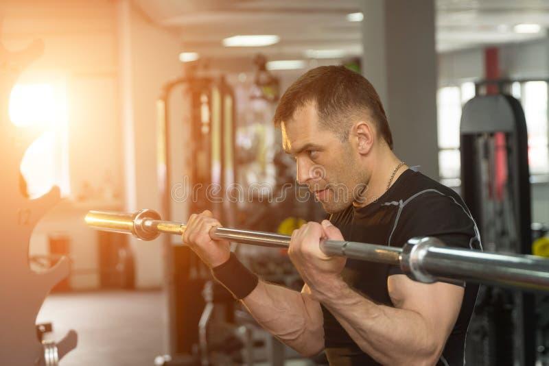 Sterke mens die met een barbell in een gymnastiek met zonlicht uitoefenen royalty-vrije stock afbeeldingen
