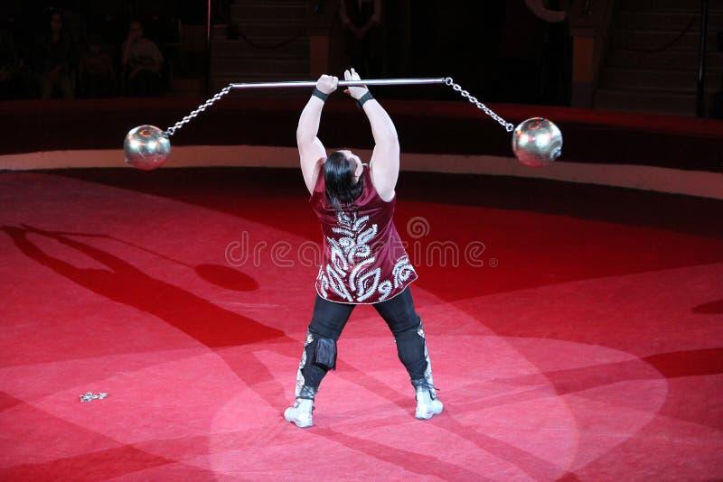 Sterke mens die trucs met gewichten op arena van circus tonen royalty-vrije stock foto's