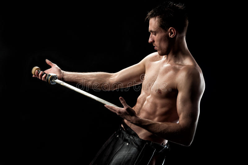 Sterke mens met oud zwaard op zwarte stock fotografie