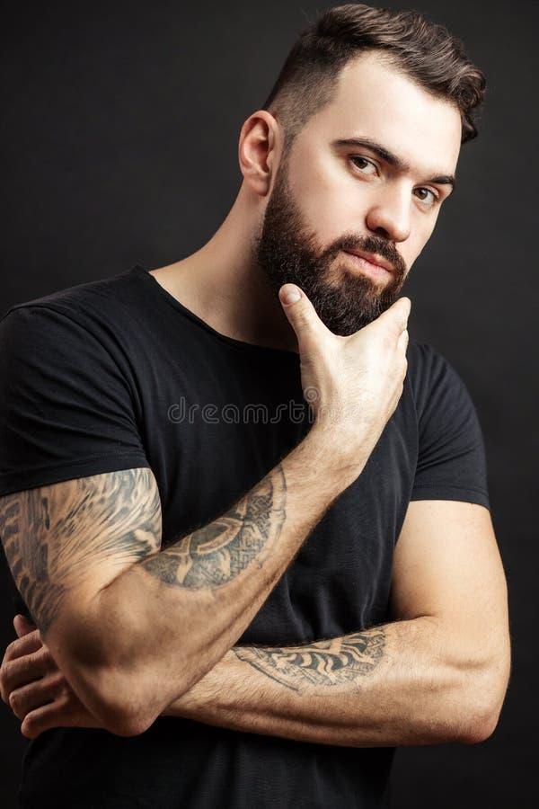 Sterke mens in zwart strak gepast overhemd met een ernstige uitdrukking op zijn gezicht royalty-vrije stock afbeelding