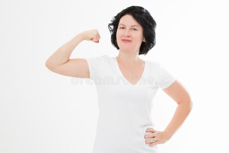 Sterke middenleeftijdsvrouw die haar gespierdheid tonen die en camera bekijken op wit wordt geïsoleerd T-shirt van het exemplaar  royalty-vrije stock foto