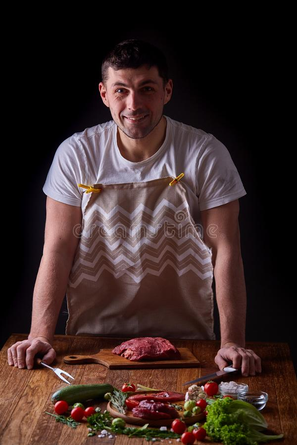 Sterke professionele mensen` s handen die ruwe biefstuk, selectieve nadruk, close-up snijden stock afbeeldingen