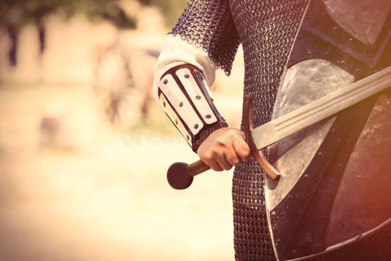 Sterke ridderhand met mooi zwaard en schild op het midden royalty-vrije stock afbeeldingen