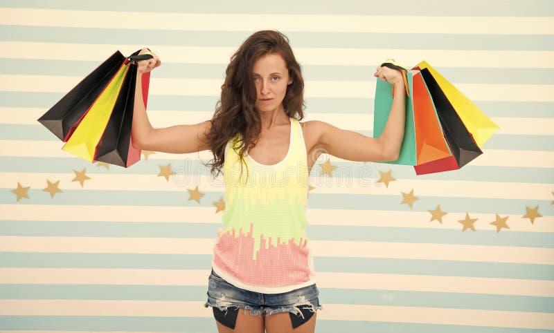 Sterke shopaholic meisjesgreep het winkelen zakken Mooie shopaholic meisje die kleurrijke document zakken in sterke handen houden stock afbeelding
