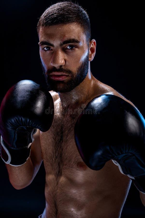 Sterke spierbokser in zwarte bokshandschoenen Een mens in een in dozen doende tribune op zwarte achtergrond royalty-vrije stock foto's