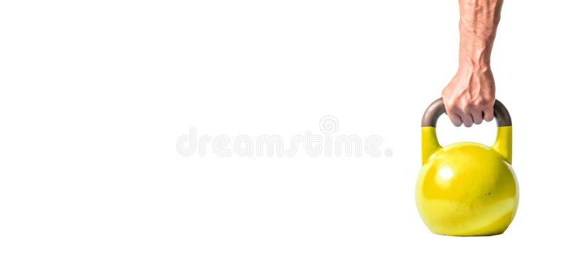 Sterke spiermensenhand met spieren die gele zware die kettlebell houden als materiaal van de gymnastiektraining gedeeltelijk op w royalty-vrije stock afbeeldingen