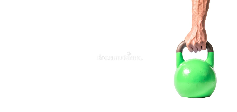 Sterke spiermensenhand met spieren die groene zware die kettlebell houden als materiaal van de gymnastiektraining gedeeltelijk op stock foto