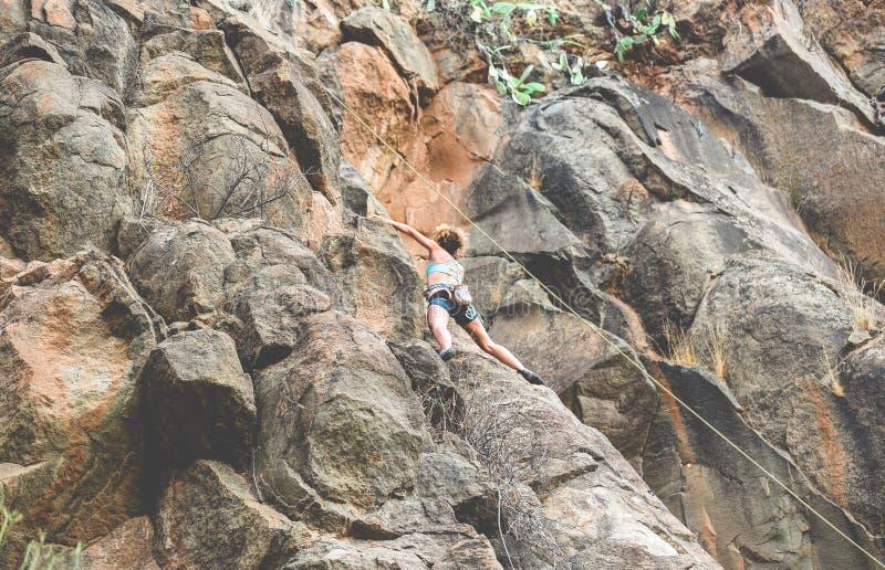Sterke vrouw die een rotswand beklimt in een canyon - Klimaattraining buitenshuis - Reis, adrenaline en extreem gevaarlijk sportc stock afbeelding