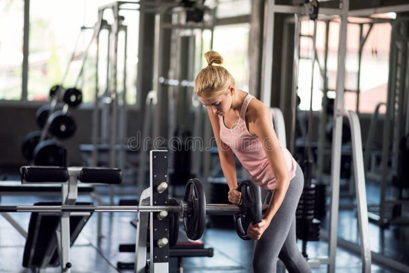 Sterke vrouw die met de plaat van het barbellgewicht in een geschiktheid c uitoefenen stock foto
