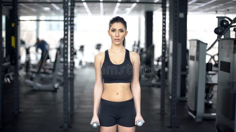 Sterke vrouw opleiding met domoren in gymnastiek, spieren die, actieve levensstijl opleiden stock fotografie