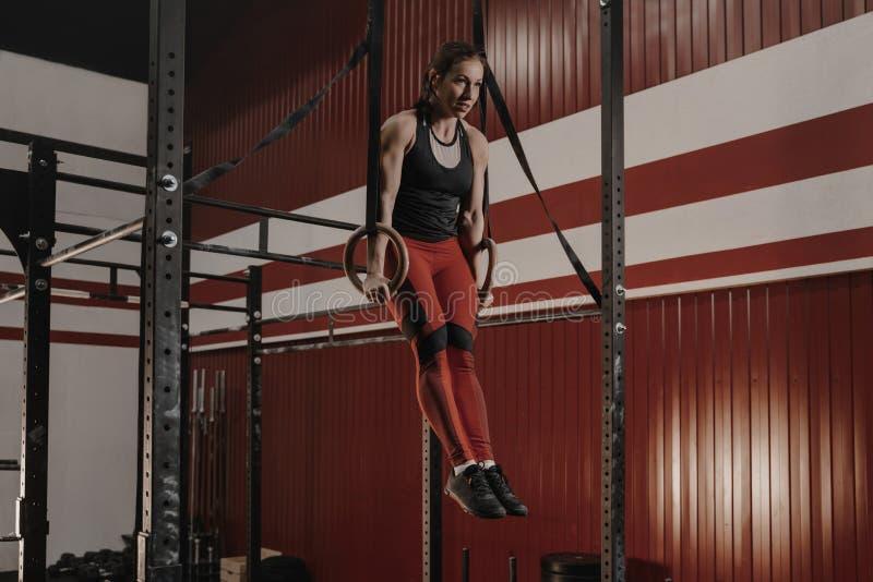 Sterke vrouwelijke atleet het praktizeren gymnastiek, die ringsonderdompelingen doen stock afbeelding