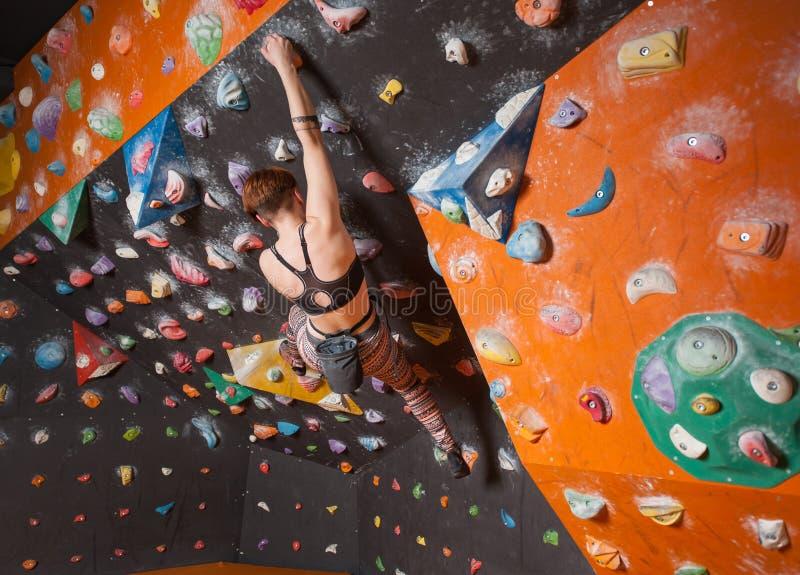 Sterke vrouwelijke klimmer die op kei muur beklimmen binnen stock foto