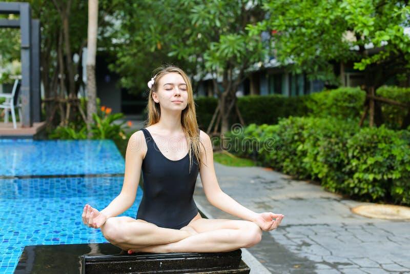 Sterke vrouwenzitting in lotusbloempositie, die yoga doen door de pool o royalty-vrije stock fotografie