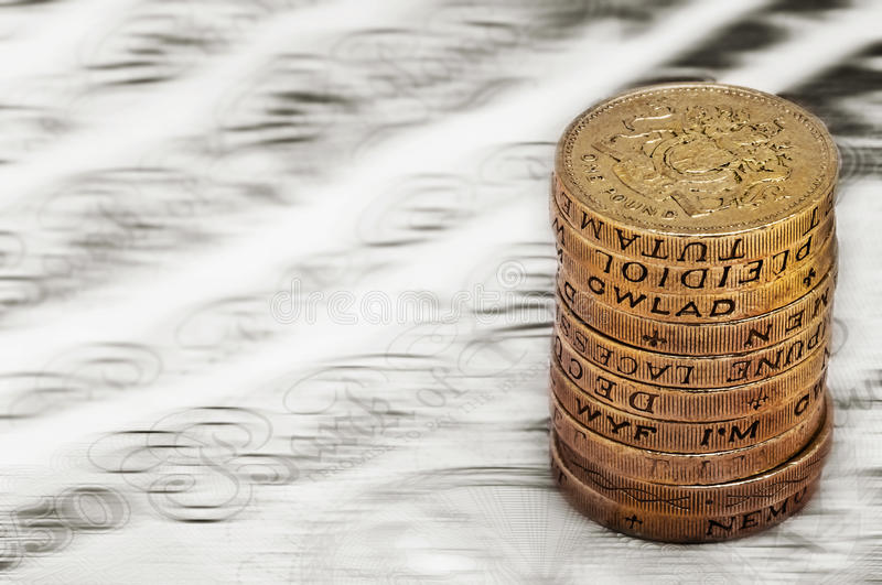 Sterling pound depreciation devaluation reduction value concept closeup macro view at UK currency stack of one pound coins royalty free stock photos