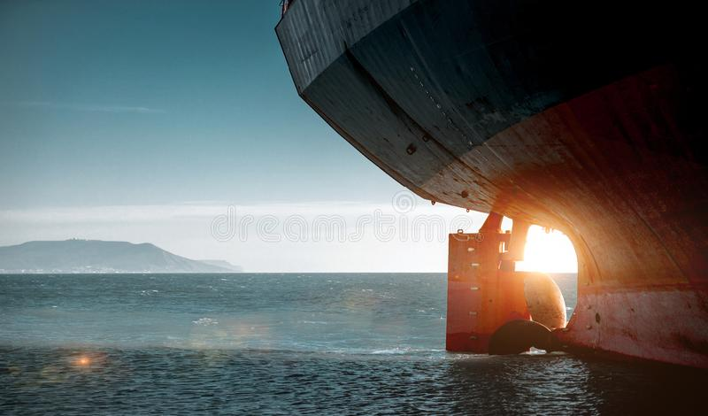 Stern of a cargo ship aground against backdrop of blue sea. World Transport Problems Freight Shipping Concept. Idea royalty free stock image