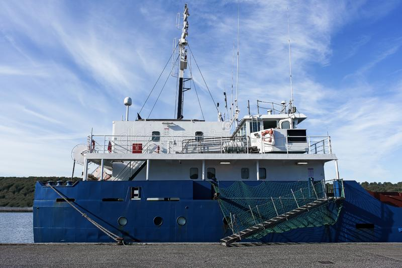 Stern of cargo vessel at port. Gangway arrangment. Blue hull. White superstructure royalty free stock photos