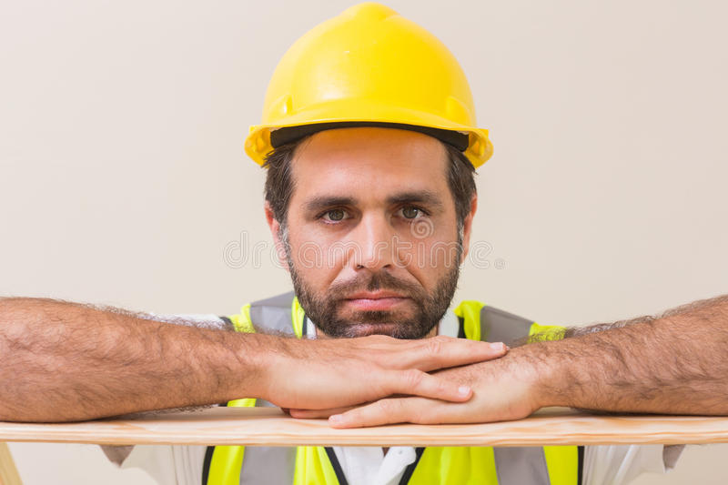Stern construction worker looking at camera. In a new house royalty free stock photos