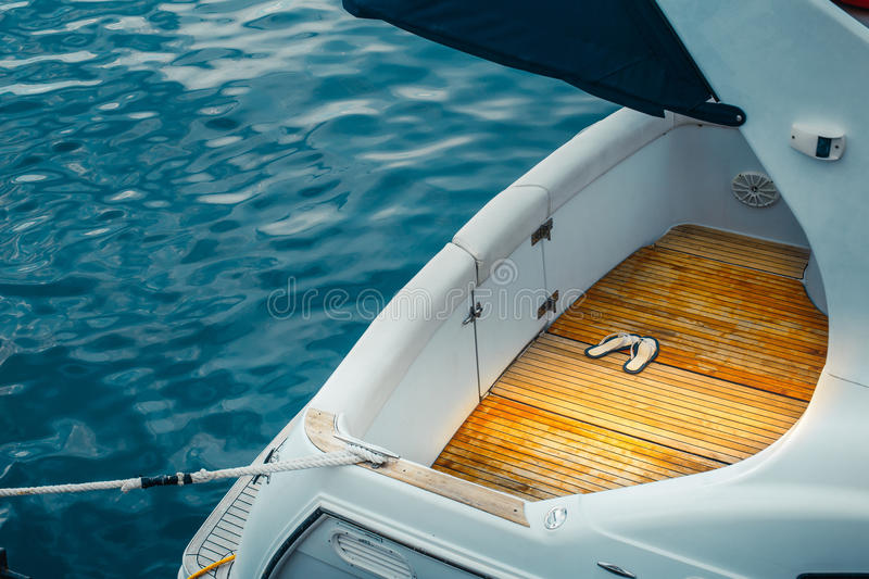 Stern Cruise Motor Yacht And Blue Sea, Closeup Sea Water Transport Concept. Stern of a motor yacht moored to shore closeup Water Transport Concept royalty free stock image