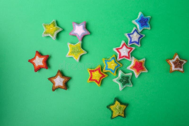 Stern des Weihnachtsneuen Jahres spielt die verschiedenen Farben die Hauptrolle von den Perlen gemacht werden, die auf grünem Hin stockbild