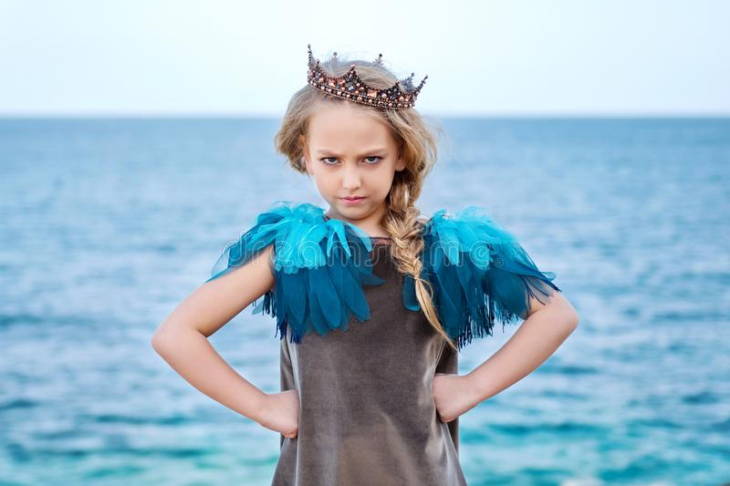 Stern little princess girl in the crown watch frowningly, stands akimbo stock images